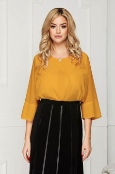 Mustard office asymmetrical loose fit women`s blouse short cut from veil fabric with metal accessories
